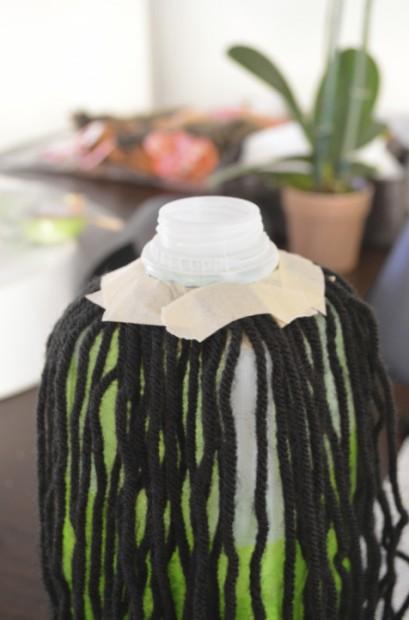 Halloween milk jug witch lantern attaching the black yarn hair MyMommaToldMe.com